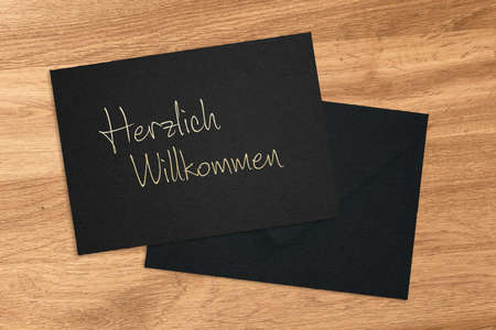 Welcome in German handwritten on a black envelope and card lying on a wood table viewed from above