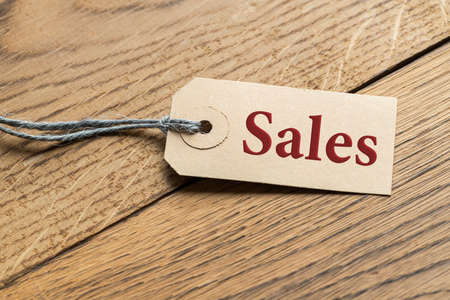 Hangtag with the word SALES on wooden background