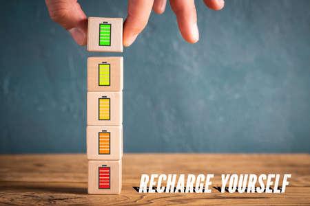 Cubes empilables à la main avec des icônes symbolisant la recharge de l'énergie mentale et le message «rechargez-vous»
