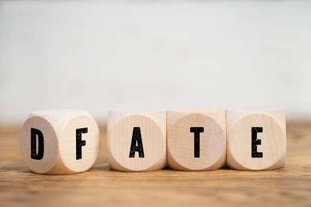 Small wood cubes with letters spelling DATE and FATE sitting on blurry wooden surface and white wall in background