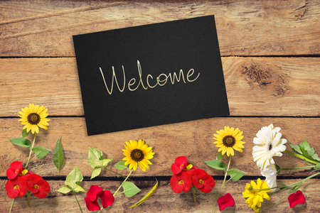 Welcome sign handwritten  on paper envelope on unpainted wooden background in welcoming concept layout with colorful flowers from rustic garden