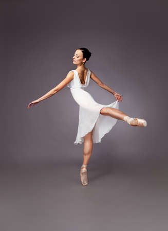 Ballerina in an elegant white dress posing gracefully en pointe on one leg over a grey background with copy space