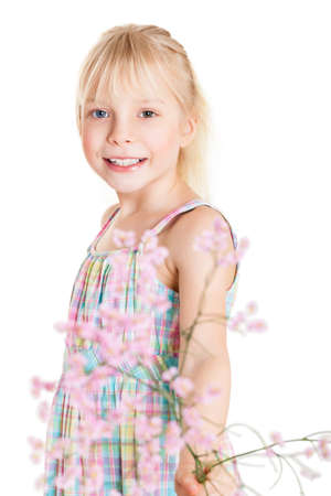 Pretty little blond girl in a sleeveless summer dress standing holding pink spring blossom with focus to her smiling face isolated on white