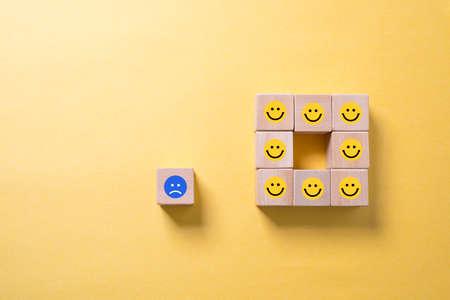 Single unhappy block and group of happy blocks symbolizing feeling lonely over illuminated orange background 版權商用圖片