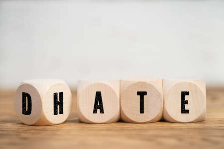 Cubes with black letters on sides placed to spell DATE or HATE symbolizing aversion and loathing on wooden table. Stockfoto