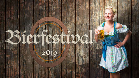 message beer festival 2019 in German beautiful woman in a traditional bavarian dirndl in front of wooden background Zdjęcie Seryjne