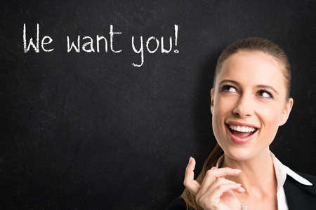 """businesswomen standing in front of blackboard with message """"We want you!"""""""