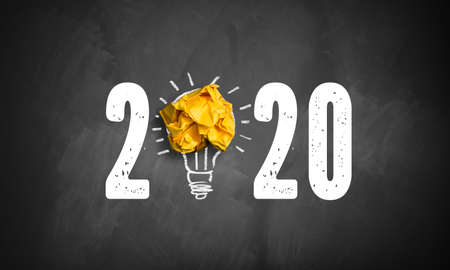 idea found for 2020 symbolized as a lightbulb out of crumpled paper on a blackboard Stock Photo