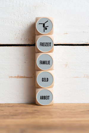 work-life balance concept with the German words for freetime, money, family, life, work on wooden cubes in front of wooden background