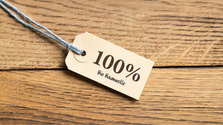 hangtag with title 100% Bio Cotton in German on wooden background Stock Photo