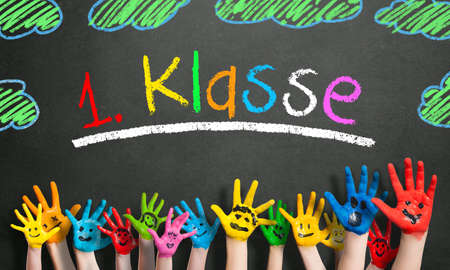 painted kids hands and the word first grade in German in colorful letters on a blackboard