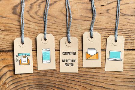 """Etiquetas colgantes sobre fondo de madera con el mensaje """"contáctenos, estamos allí para usted"""" sobre fondo de madera"""