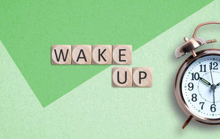 classical copper colored alarm clock with bells in a Wake Up concept on paper background with text