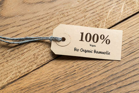 hangtag with title 100% Bio Organic  Cotton in German on wooden background Stock Photo