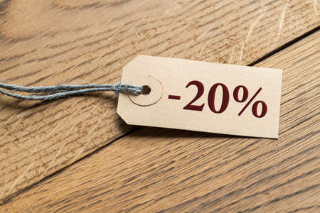 Hangtag with title -20% on wooden background