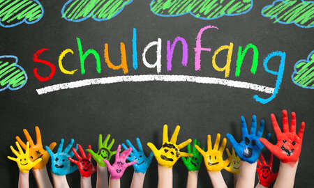 painted kids hands and the word first day at school in German in colorful letters on a blackboard
