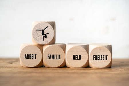 """Work-Life-Balance-Konzept mit den deutschen Wörtern für """"Freizeit, Geld, Familie, Leben, Arbeit"""" auf Holzwürfeln vor Holzhintergrund Standard-Bild"""