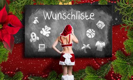 attractive blonde miss santa in front of a blackboard with a wishlist Zdjęcie Seryjne