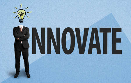 businessman with lightbulb as a head and the word innovate on paper background