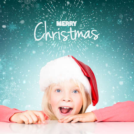 young girl with christmas hat on blue background with Merry Christmas message