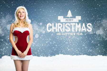 attractive blonde miss santa with merry christmas message in front of blue background Zdjęcie Seryjne