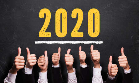 many thumbs up in front of blackboard with message 2020