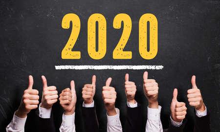 wiele kciuków w górę przed tablicą z komunikatem 2020