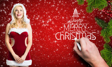 attractive blonde miss santa with merry christmas message in front of red background