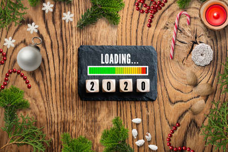 slate plate with message loading 2020, surrounded by christmas decoration