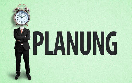businessman with alarm clock as a head and the German word for planning on paper background 版權商用圖片