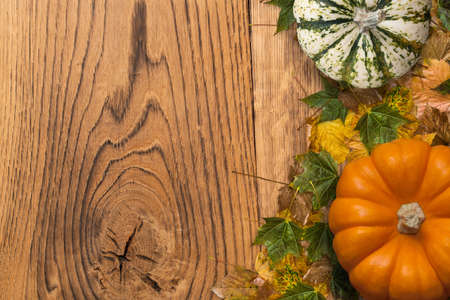 Autumn decoration with fallen leaves and pumpkin on wooden background