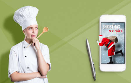 Smartphone with running Santa and christmas recipies and a cook in front of paper background Archivio Fotografico - 133767766