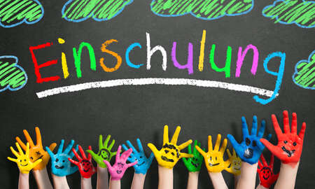 painted kids hands and the word school enrollment in German in colorful letters on a blackboard