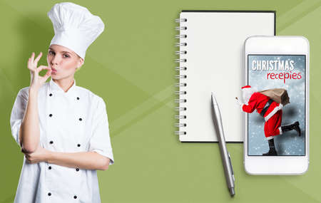 Smartphone with running Santa and christmas recipies and a cook in front of paper background Archivio Fotografico - 133767645