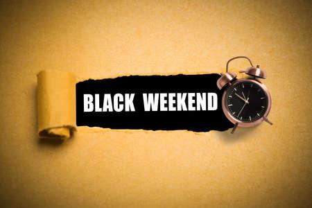 torn paper reveals black weekend on black background