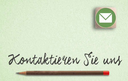 "German message for ""contact us"" and a pen on paper background"