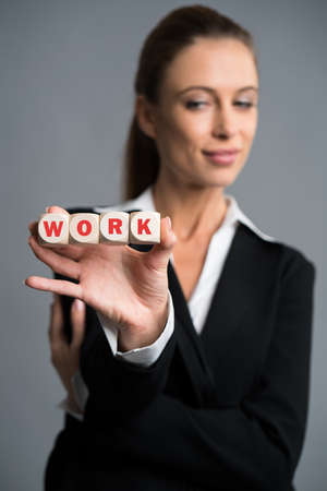 businesswoman holding cubes with the word WORK in front of grey background