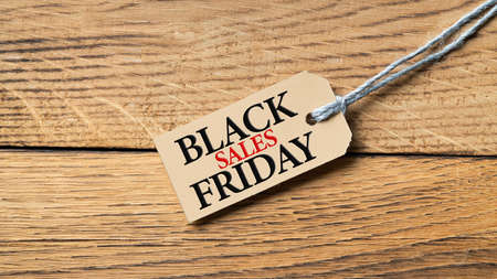 Hangtag with text Black Friday on wooden background