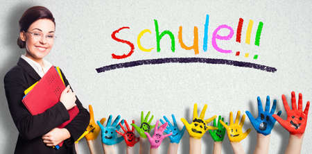 teacher and many painted kids hands with smileys and the message school!!! in German in colorful letters on a wall Stock Photo