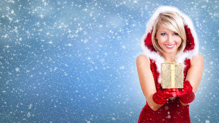 attractive miss santa with a gift in front of winter background