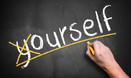 """Hand kreuzt einen Buchstaben auf der Tafel und ändert das Wort """"sich selbst"""" in """"unser selbst"""" Standard-Bild"""
