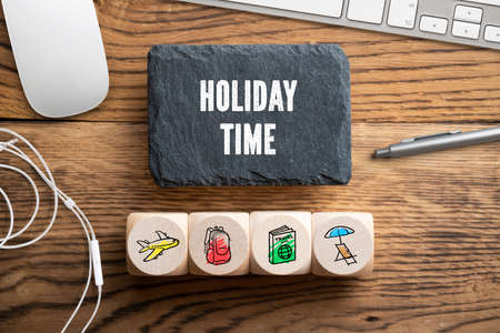Message Holiday time depicting online travel concept with travel icons on wooden background 版權商用圖片
