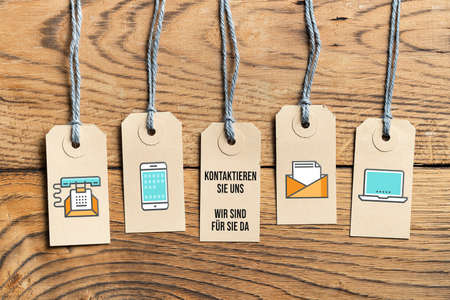 "Hangtags on wooden background with German message for ""contact us, we are there for you"" on wooden background"