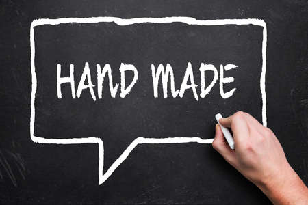 "hand writing ""hand made"" in speech bubble on a blackboard"
