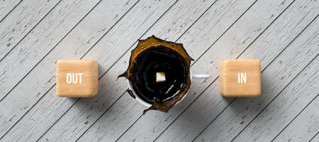 cup of coffee and cubes with the words OUT and IN on wooden background - 3D rendered illustration