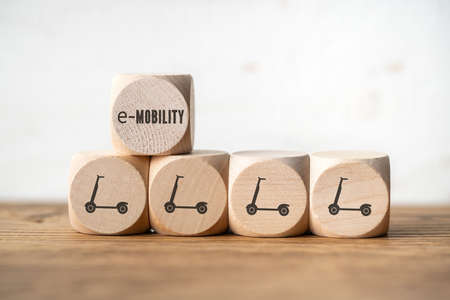 cubes with electric kick scooter symbols on wooden background