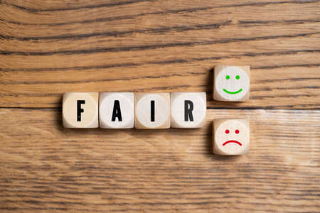 """cubes with the word """"fair"""" and decision between happy or sad smiley on wooden background Stock fotó"""