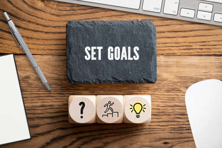 SET GOALS - idea concept in an office scene on wooden background 写真素材