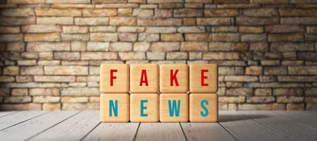 cubes with the words FAKE NEWS in front of a brick wall - 3D rendered illustration