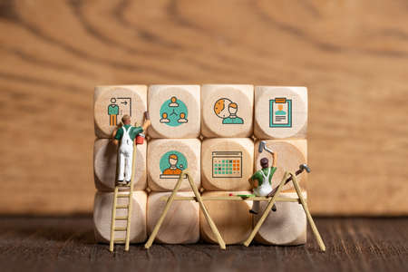 cubes with business Icons and a painter figure on wooden background
